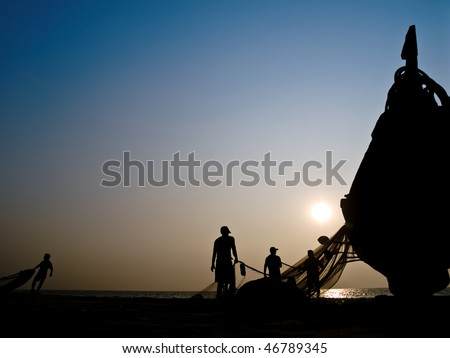 Silhouette of fishers boat against a sunset and blue sky on the sea - stock photo