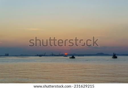 silhouette of fishing boat and sunset, with  koh sichang and sriracha harbour background