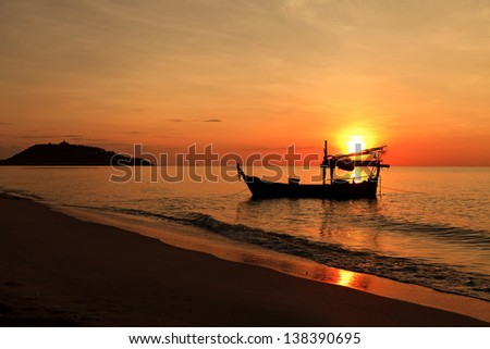 Silhouette of fishing boat at sunset - stock photo