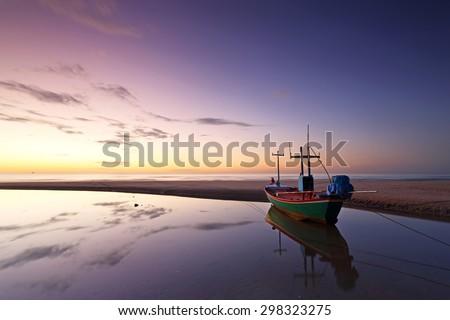 Silhouette of fishing boat with water reflection in beautiful sunrise at Cha-am beach Phetchaburi, Thailand - stock photo