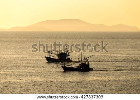 silhouette of fishing boats on ocean water - stock photo