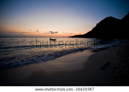 Silhouette of fishing boats resting on the sea under the view of a perfect sunrise on a tranquil deserted beach