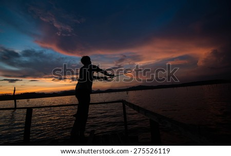 Silhouette of fishing man in the lake - stock photo