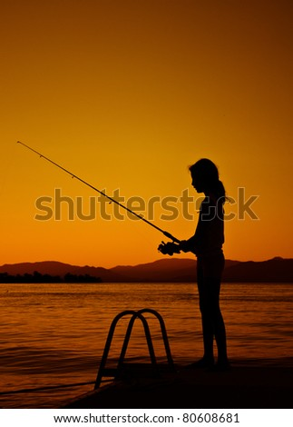 silhouette of fishing young girl at lake