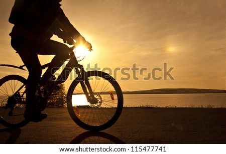 silhouette of fit cyclist in cap at sunset with a blurred reflection in water with ripples ride along seashore summer beach at yellow evening horizon sea sunset cloudy sky background Outdoor - stock photo