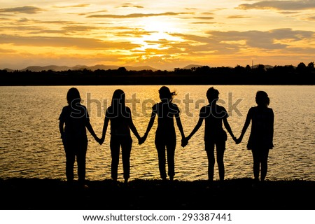 Silhouette of five friends in the evening at the beach, holding hands and waiting for the sunset. Support, together, winning, helping, freedom concept.