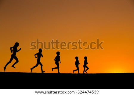 silhouette of five kids running on the beach against sunset