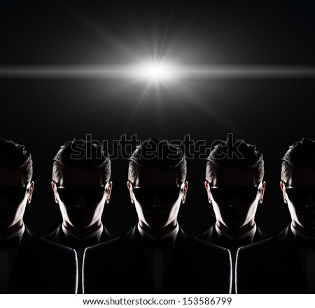 silhouette of five young men in a jacket on a black background in studio - stock photo