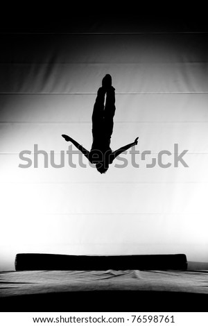 silhouette of flying man on trampoline - stock photo