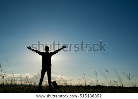 silhouette of free cheering with his arms wide open with sunset,sunrise blue sky on background
