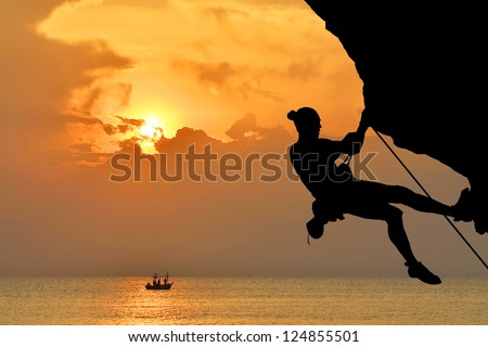 silhouette of free-climber in sunset - stock photo