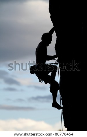 silhouette of free climber on rock - stock photo