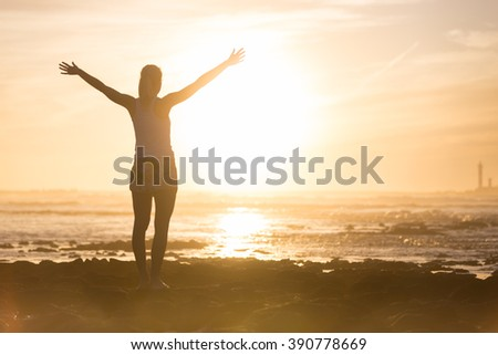 Silhouette of free woman enjoying freedom feeling happy at beach at sunset. Serene relaxing woman in pure happiness and elated enjoyment with arms raised outstretched up.  - stock photo