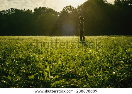 silhouette of free young woman at sunrise with forest background - stock photo