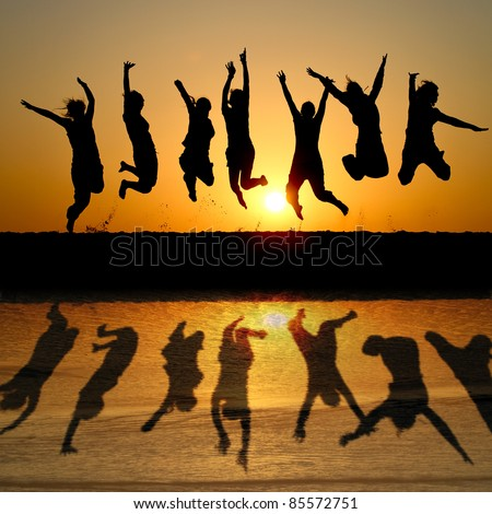 silhouette of friends jumping in sunset at beach with reflection in water - stock photo