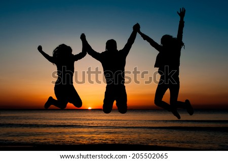 silhouette of friends jumping on beach during sunrise time - stock photo