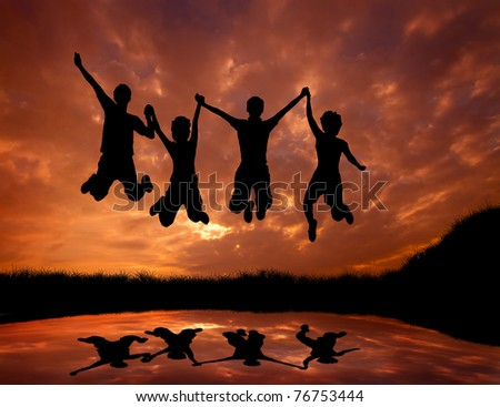 silhouette of friends jumping with joy at sunset - stock photo