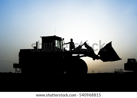 Silhouette of front end loader and worker in construction site at oilfield - sunset