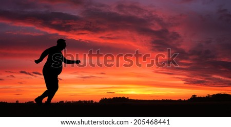 Silhouette of funny overweight man jogging at the sunset - stock photo