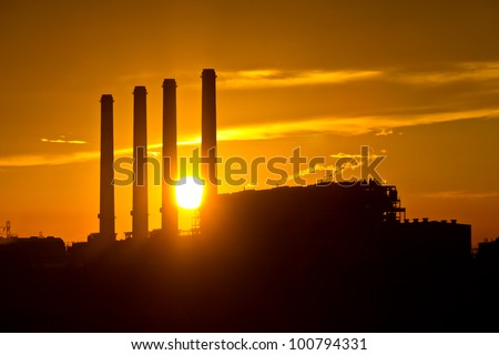 Silhouette of gas turbine electrical power plant against sunset - stock photo