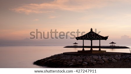 Silhouette of gazebos at Sanur beach against the morning twilight soft color sky.  Long exposure photography for first day light serene seascape with Mount Agung at the background. - stock photo