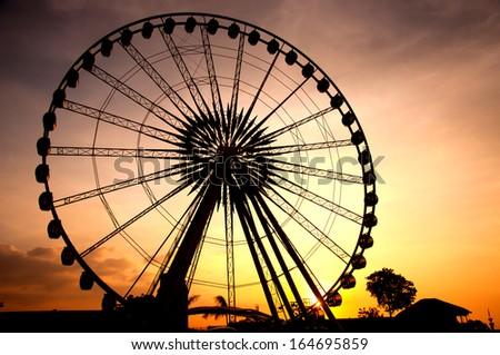Silhouette of giant ferris wheel  - stock photo