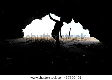 Silhouette of girl cautiously exploring cave on a beach along the Na Pali Coast of Kauai, HI
