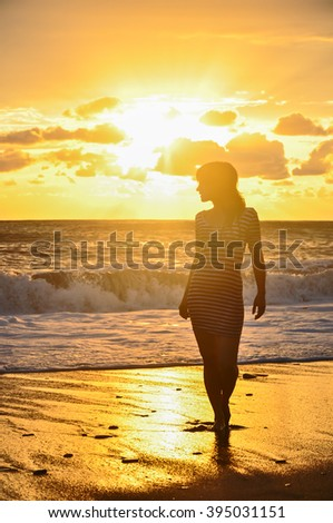 Silhouette of girl in frock standing in sea at golden sunset background - stock photo