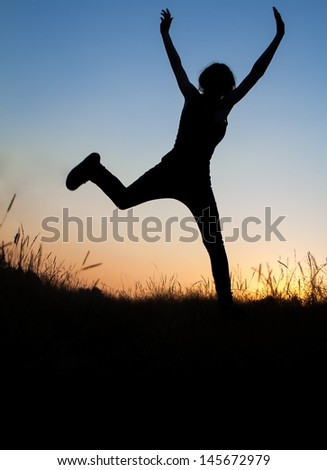 Silhouette of girl jumping in field - stock photo