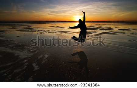 silhouette of girl jumping on beach in sunset