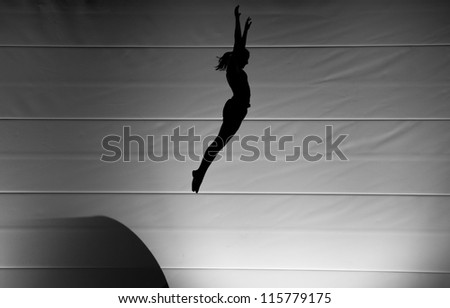 silhouette of girl jumping on trampoline - stock photo