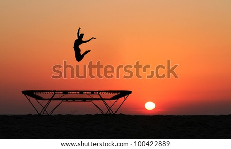silhouette of girl jumping on trampoline in sunset - stock photo
