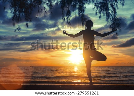 Silhouette of girl meditating on the sea beach during a wonderful sunset. Yoga and fitness. - stock photo