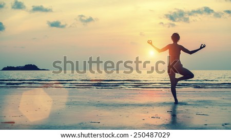 Silhouette of girl meditating on the sea beach. Yoga and fitness. - stock photo