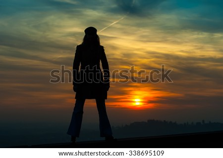 Silhouette of girl standing on the wall wading red sunset