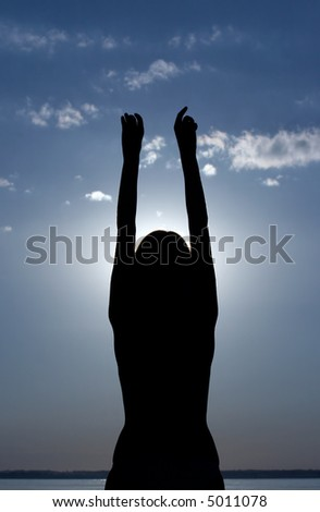 silhouette of girl with hands raised up on sunset sky background - stock photo