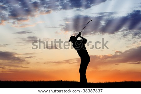 Silhouette of golfer mid-swing - stock photo