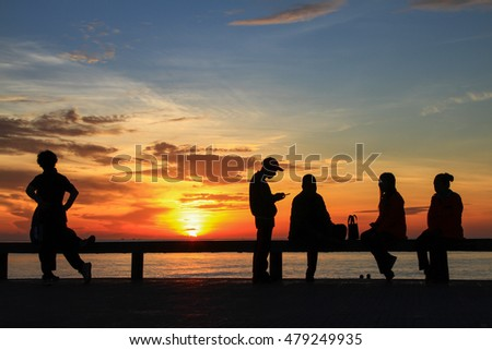 Silhouette of group in the morning at the beach waiting for the sunrise.