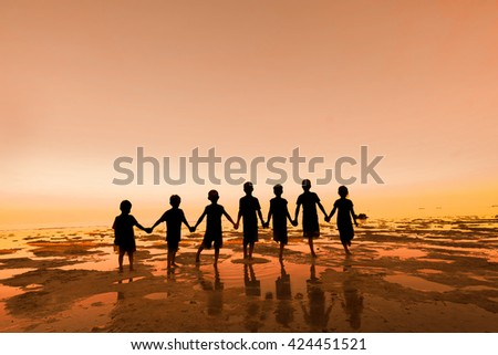 Silhouette of group kid, people stand on beach with warm tone  - stock photo