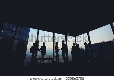 Silhouette of group of young skilled business people talking among themselves while standing in modern office interior near window, mans and women's purposeful bookkeepers discuss ideas after meeting - stock photo