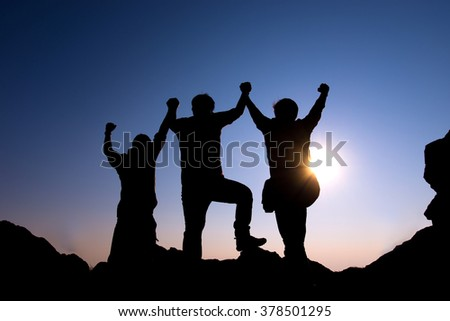 Silhouette of group people on the peak of rocks mountain at sunset with arms raised up above head in celebration - stock photo