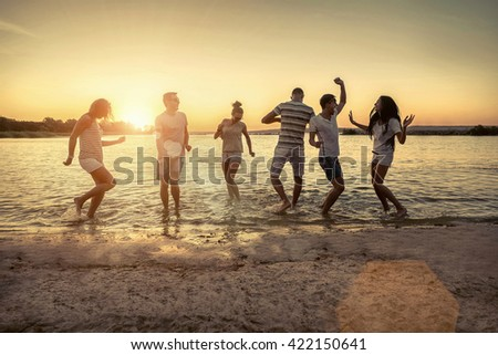Silhouette of group young people on the beach. - stock photo