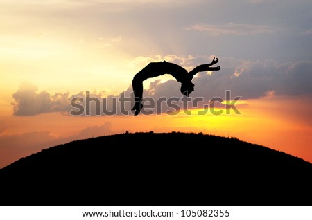 silhouette of gymnast jumping on hill in sunset - stock photo