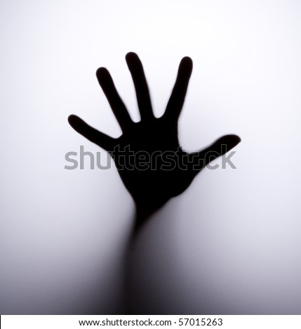Silhouette of hand behind glass foreground - stock photo