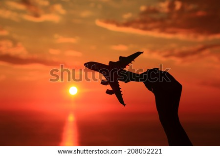 Silhouette of hand holding airplane miniature with sunset background