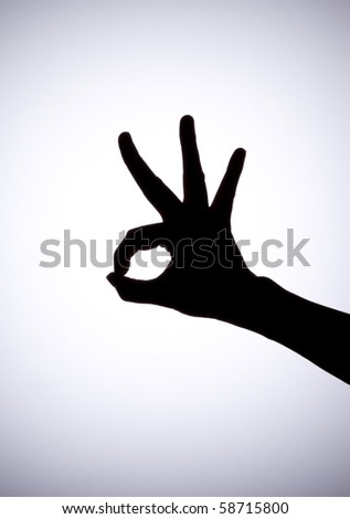 "Silhouette  of hand making gesture ""OK"" - stock photo"
