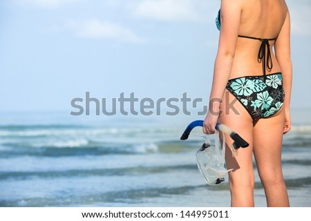 Silhouette of hand with equipment for snorkeling, on the beach (picture with space for text) - stock photo