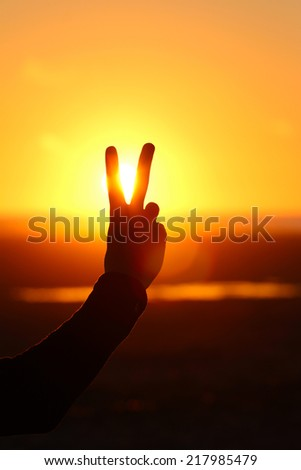 Silhouette of hand with two fingers at sunset with ocean background - stock photo