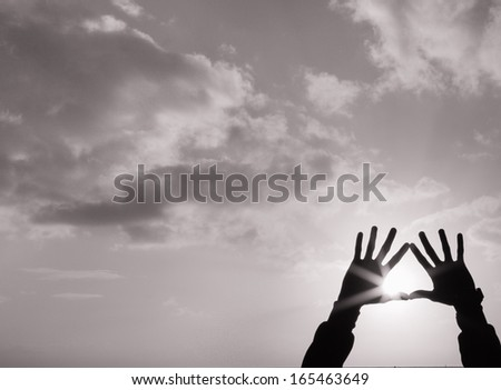 Silhouette of hands holding up the sun