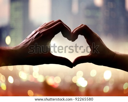 Silhouette of hands in form of heart when sweethearts have touched - stock photo